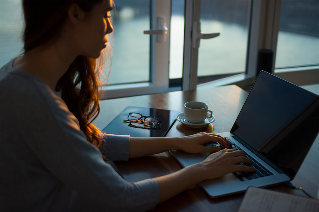 Girl Sitting at Desk with Laptop